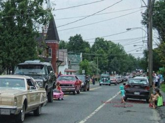Little girl driving a little pink car in vintage vehicule parade.