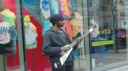 """On the Move"" musically talented busker playing electric guitar."