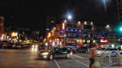 Lights twinkle off glossy surfaces at corner of busy Crescent Street.