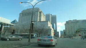 An early bird  travelling East downtown approaching a cluster of famous Montreal landmarks.