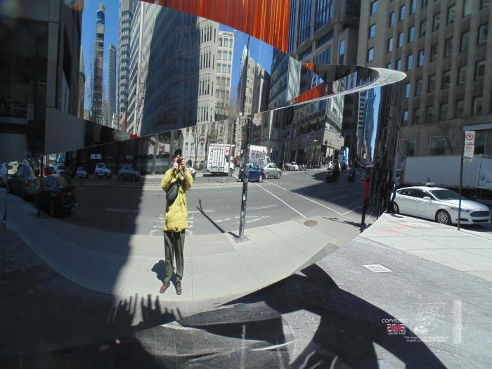 The wrap mirror in downtown Montreal is actually a piece of modern art made of polished stainless.