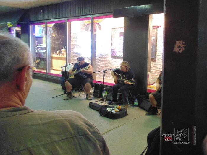 Three cash hopeful Montreal buskers play rock n roll music on Saint Catherine street on busy July night for crowd.