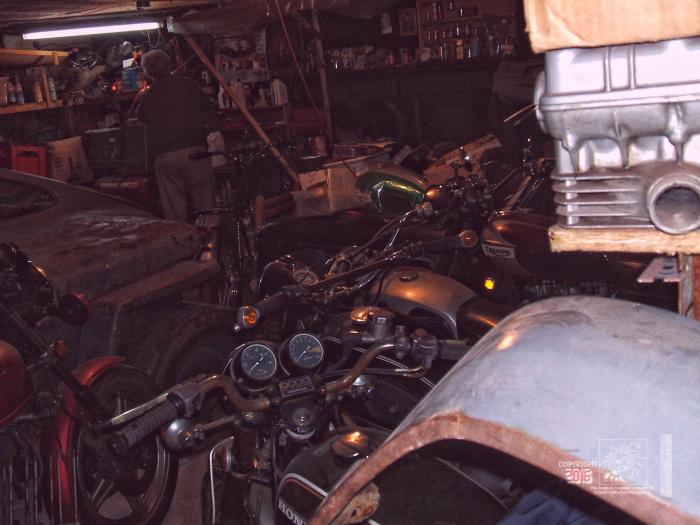 "A dark damp cluttered interior filled with parts and myriad of ""projects"" awaiting restoration work."
