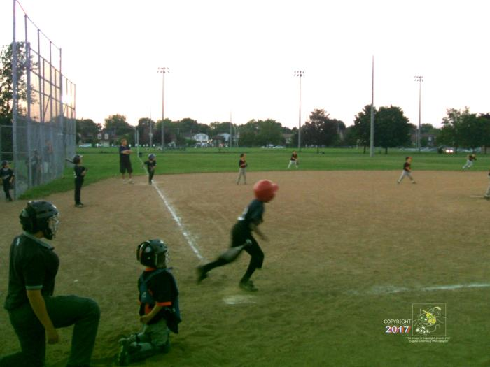 Little league batter whacks slow ball for successful base hit.