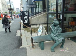 Mother breast-feeding child has scant privacy on busy Sherbrooke street in downtown Montreal.