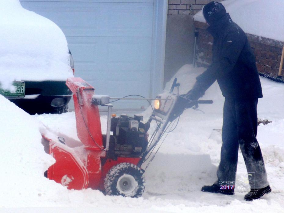Man knows how to conquer winter snow using powerful snowblower to clean his driveway.