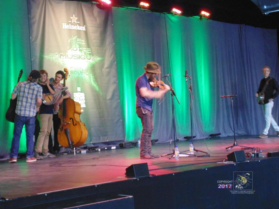 Bearded guy wearing Stetsin fiddling while around him band members seem in controversy.