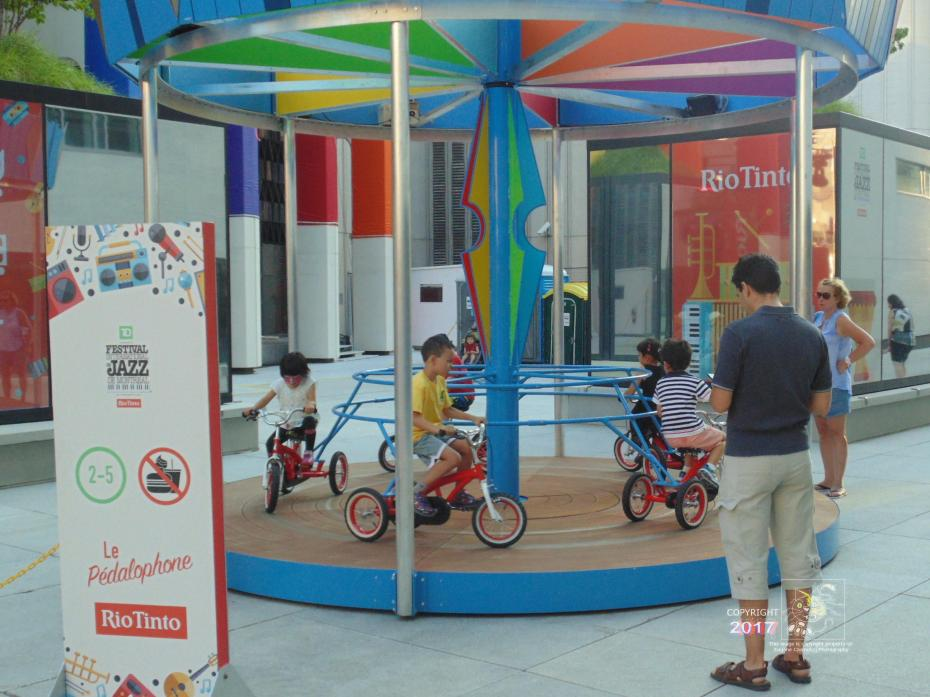 Children amused by Le Pedalophone in Montreal's Quartier-des-Spectacles territory during Jazz Festival.
