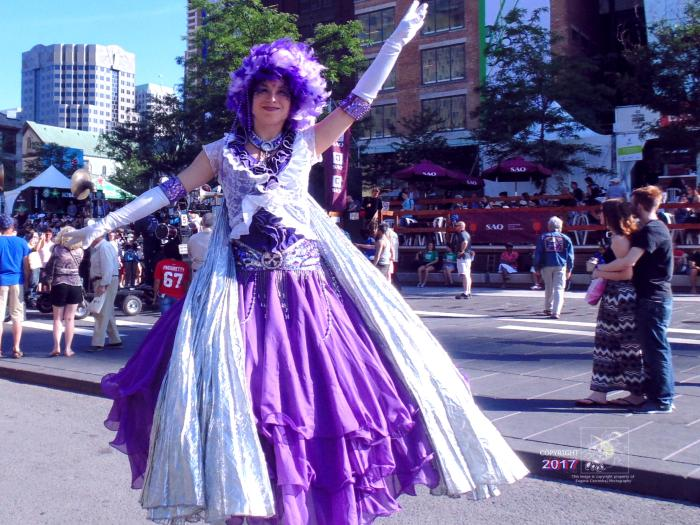 Tall purple princess in Quartier-des-Spectacles extending her royal greetings during 2016 Montreal International Jazz Festival.