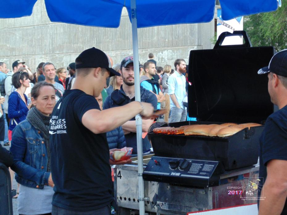 Customers on cusp of satisfaction, await patiently moment to savor own nice, fat, juicy, mouth-watering, barbecued 100% beef hot dog.