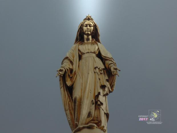 Top of gold statue of Our Lady of Lourdes reflects and shines under gray sky over Notre-Dame-de-Lourdes chapel.