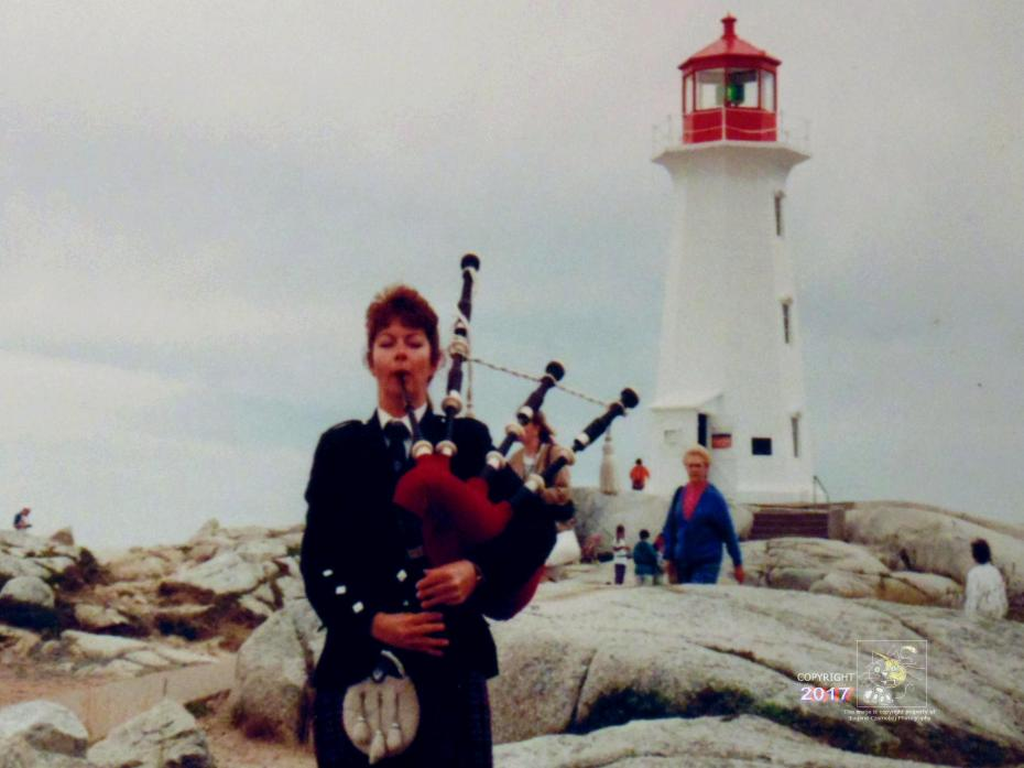 Nova Scotia wanderlust happens looking at old picture of lone Highland piper playing, with Peggy's Cove lighthouse behind her.
