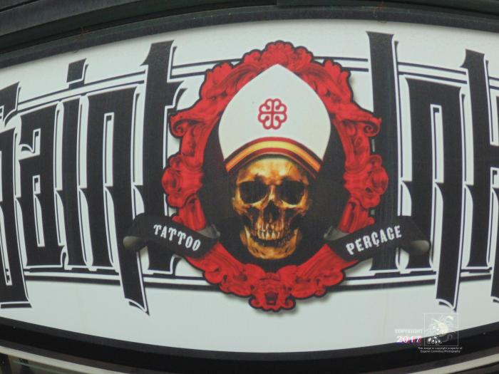Pleased skellum adorns top of tatoo and body piercing shop on Saint Catherine street its brown-colored death head smiling.