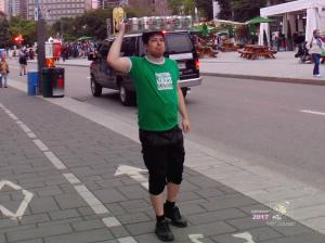Liquid hospitality delivered by strong young man in green Montreal Jazz Festival tee-shirt at Quartier-des-spectacles.