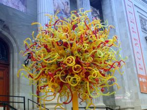 Multi-colored maze ball of plastic tubes attached to yellow metal pole on grey metal stand near Montreal Museum of Fine Arts.