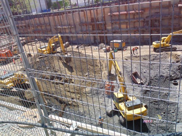 "At precipice steel fence separates passersby and huge hole by foreign ""investor"" money for expensive condominium highrise."
