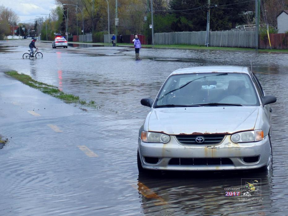 "Temporary immersible car was a submerged obstacle in dirty, polluted waters of Pierrefonds boulevard ""lake"" as area flooded."