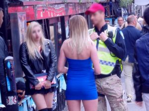 Two alleged brassy babes talk to policeman on Crescent Street last year during annual Montreal Grand Prix weekend.