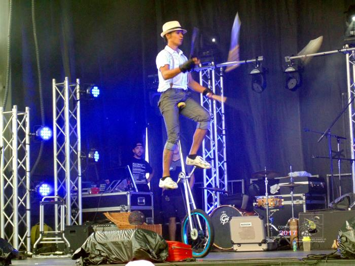 Act is no illusion as white Stetson man and woman partner juggle huge knives between each other riding rain slicked stage on unicycles.