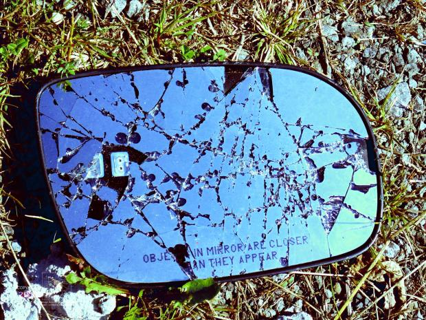 Driver-side car mirror lies shattered in field, small bits missing from high polish surface perhaps result of a car wreck.