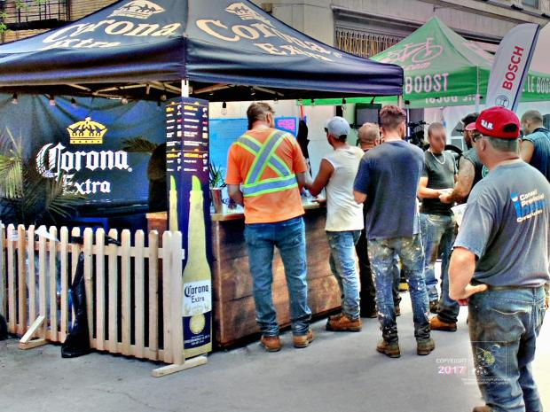 Some thirst relieved workers hang around Corona Extra kiosk enjoying plastic glass of Corona Extra others wait in line.