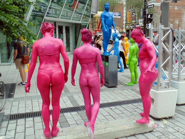 Colored savage culture shock grips downtown Montreal as blue, green, red and yellow people suddenly appear on the street.