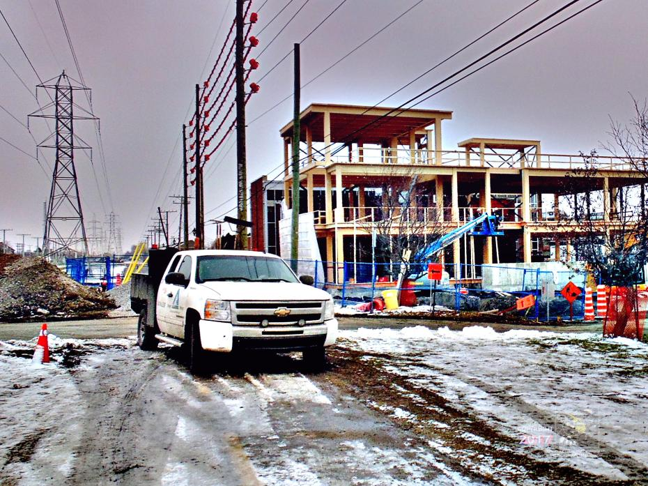 Winter season already frozen soil and light snow dusting doesn't stop work at Dollard-des-Ormeaux construction site.