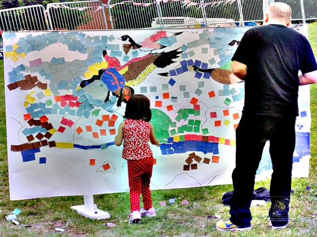 Little girl's collage uses multi-color self-adhesive squares to add color to her master piece marking Canada's 150th birthday.