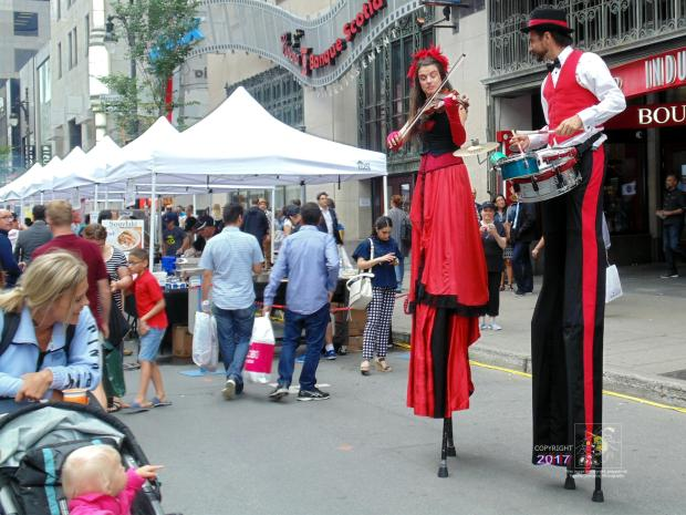 """Mommy who's their tailor?"" seems what little boy in baby carriage is saying about two tall musical buskers."