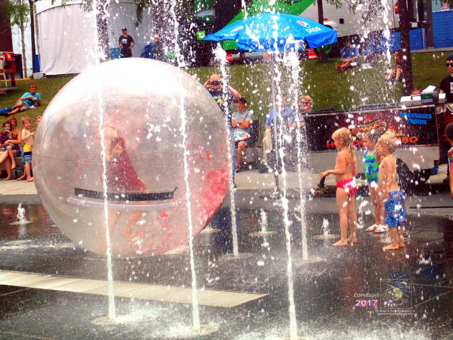 Woman in ball in water fountain caper at Quartier-des-Spectacles amuses young children, parents, and onlookers.