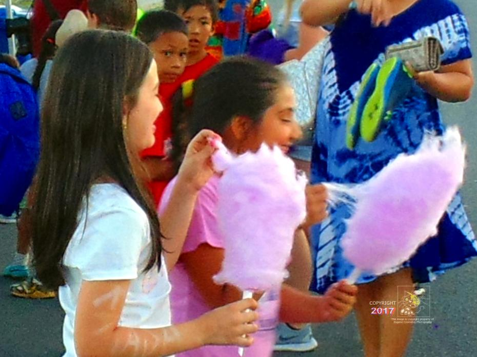 Two young girls enjoying their cotton candy conclude it's much better than a lollipop and so yummy soft.