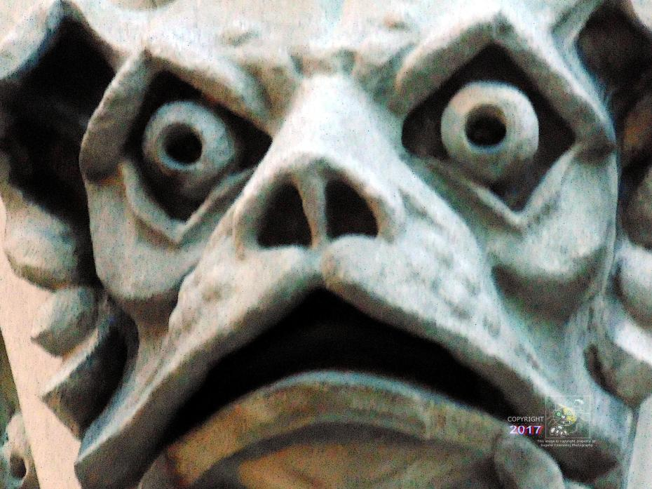 Glaring gargoyle creature stares down on passersby from facade of Christ Church Cathedral in Montreal.