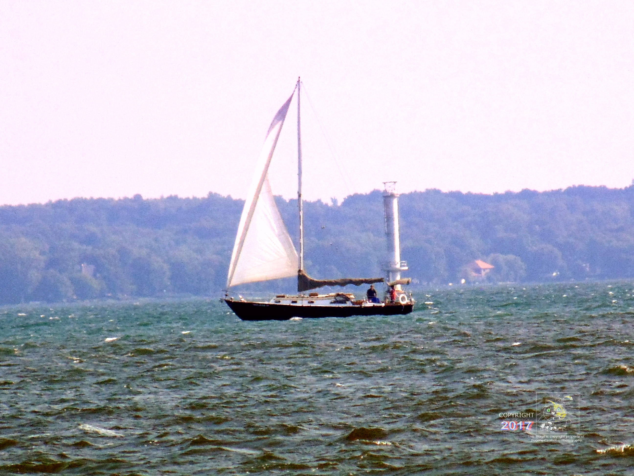 Two man crew prepare to unfurl second main sail of small sailing craft on Lac Saint Louis as winds pick up.