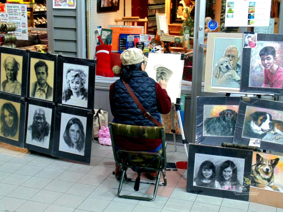 Very artistically talented solitary shopping center mall artist creates charcoal portrait of black man.