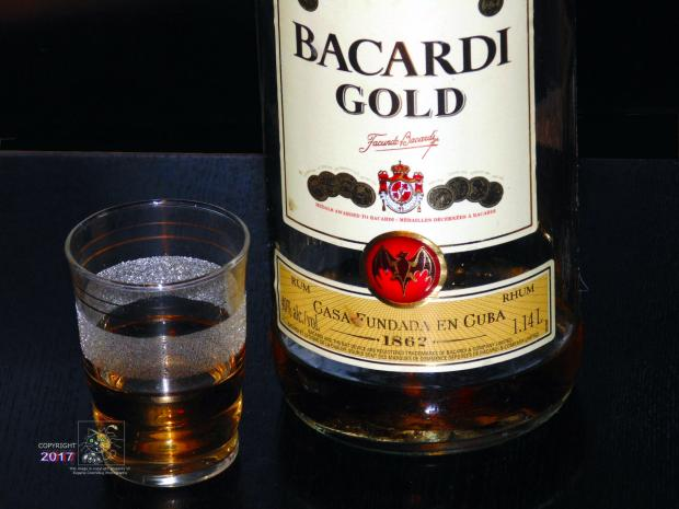 Only finite amount of Bacardi Gold remains, in shot glass and rest in large size colorful decal decorated glass bottle.