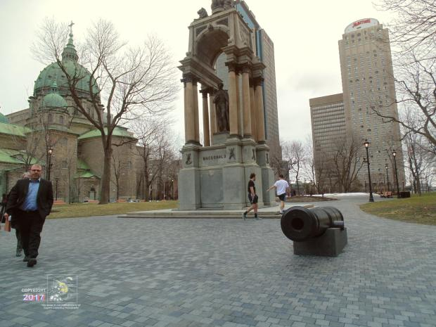 Two Montreal office workers seem about to cross line imaginary of fire of centuries old black power artillery piece in park.