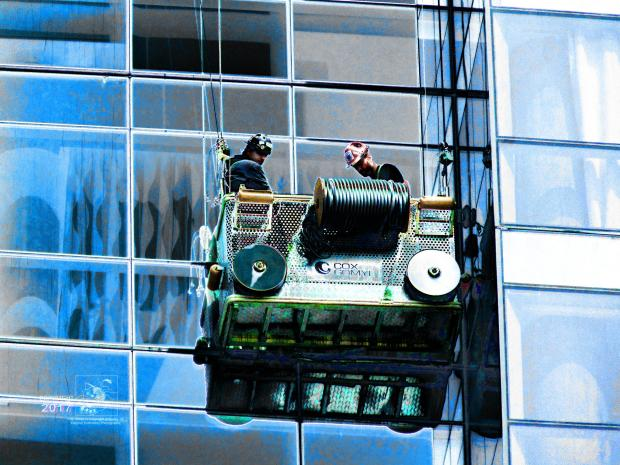 Installing highrise windows is tricky however, two construction workers are oblivious to height.