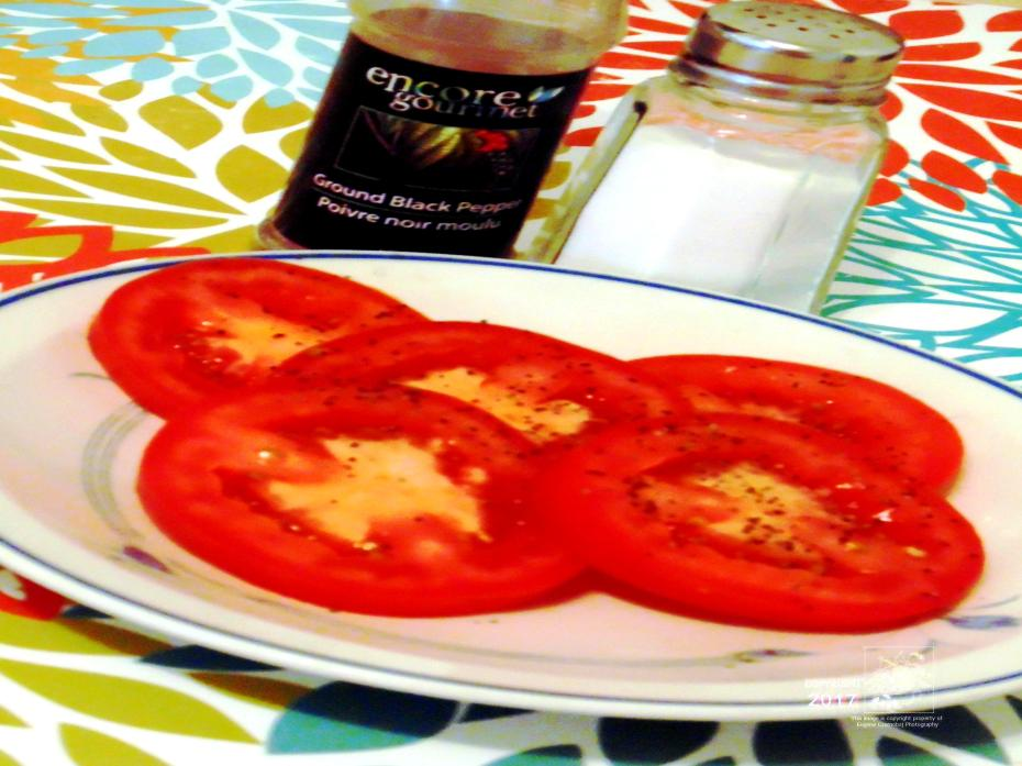 Plenty of rounded shapes in photo including rounded fruit plate of sliced spiced red tomatoes.