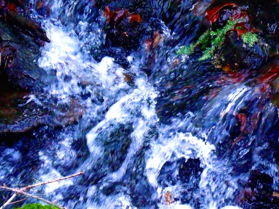 Rushing, fresh, mountain water sparkle caused by bright autumn day's sunlight reflection off its spray.