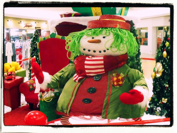 Seasonal girlie elegance very apparent as female mannikin struts her colorful winter wear for shoppers.