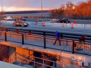 About to set, sun's intense, bright, light illuminates busy MacDonald-Cartier Bridge and surrounds.