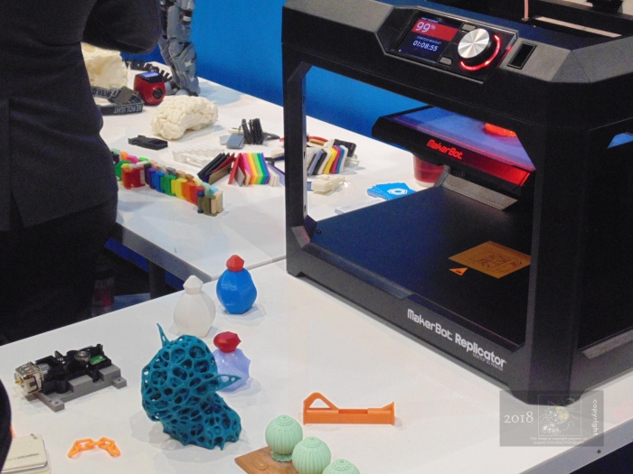 Small identical plastic things rest on exhibitor's table next to 3D printer.