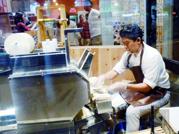 Oriental restaurant worker on special machine is in no rush producing noodles.