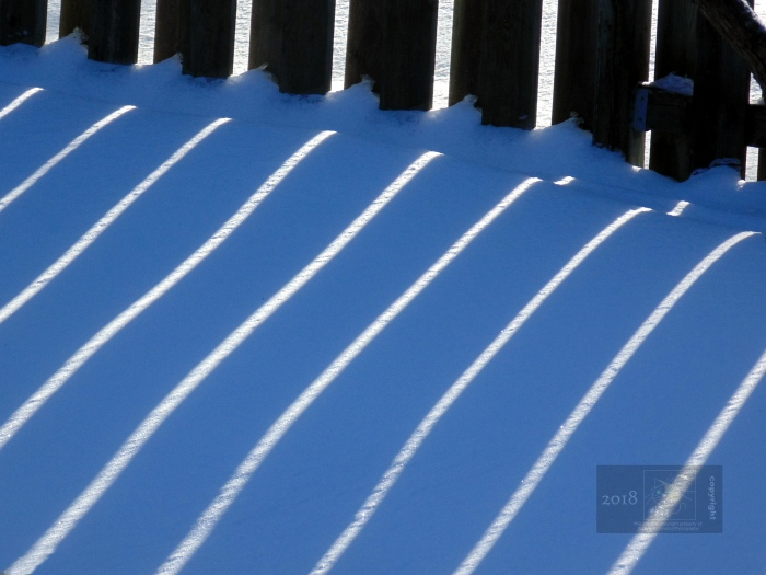 Parallel lines of intense bright February sunlight appear on light blue colored snow in shadow of home.