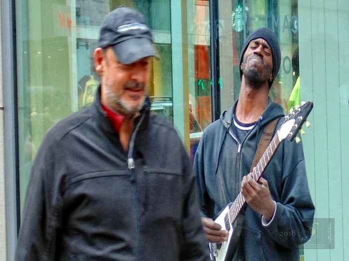 Busker playing with glimmer of hope passerby will donate money after hearing music.