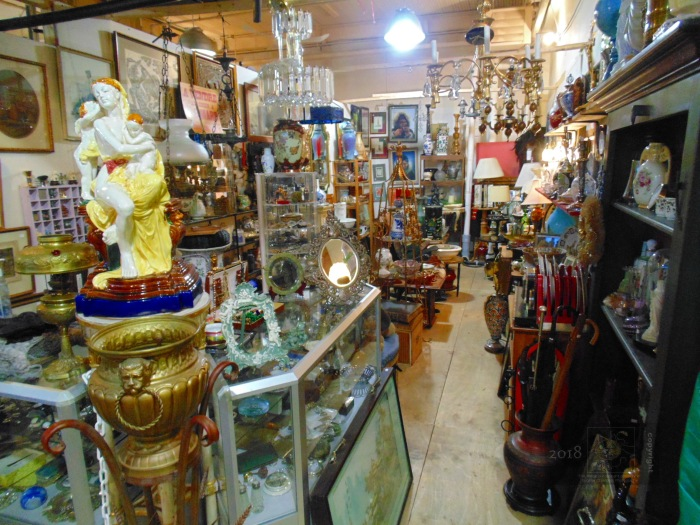 Prolific knick-knack collection of assorted baubles, novelties, cheap art etc., fill flea-market kiosk.