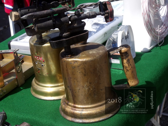 Old fashioned brass blowtorches juxtapose on vendor's table at Saint Eustache outdoor flea market awaiting buyers