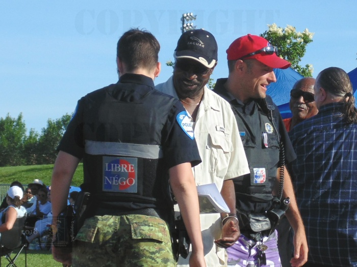 Montreal Police wearing red baseball hats, camo pants, and protest stickered vests display controlled laughter sharing a joke.