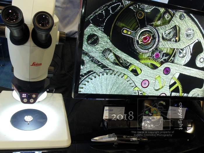 Mechanical watch core magnified appears large on computer screen connected to Leica brand digital optical comparator-microscope.