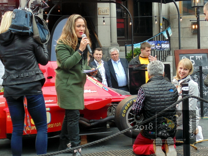 CTV woman announcer seems to blush while on mike during pre-amble to F1 racer tire change contest start as both contestants wait.